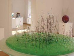 """Blick in die Ausstellung, im Vordergrund Jaroslav Matous """"Der Tümpel"""", 2003, Schmelzglas, Draht / © J. Matous, Prag"""